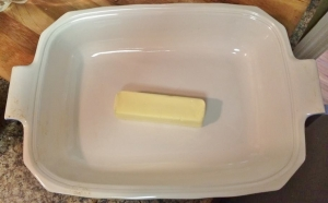 Just plop the butter right in the middle before you put it in the oven. It will spread all on its own.